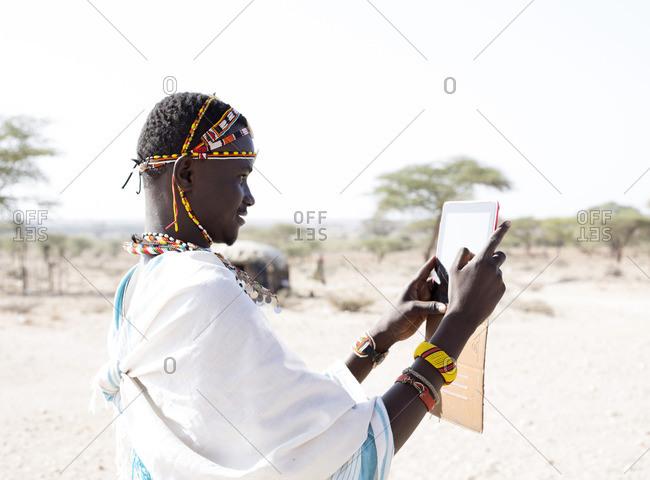 Samburu Warrior using tablet computer, Kenya