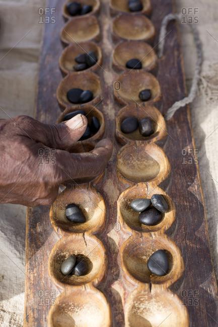Samburu tribesman playing traditional game, Kenya