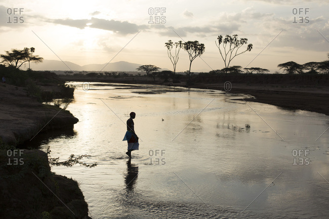 Samburu tribesman wading across river at sunrise, Kenya