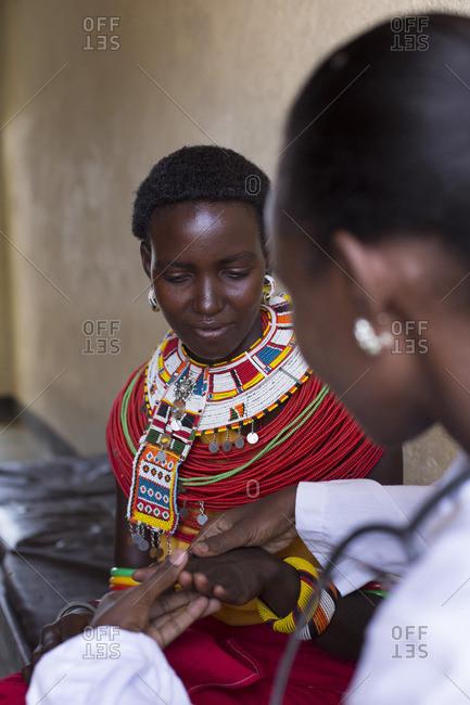 Doctor examines female Samburu patient, Kenya, Africa