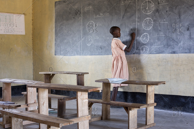 Young girl writing on chalkboard in Kenyan schoolroom