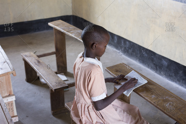 Elevated view of young girl writing in notebook in classroom, Kenya