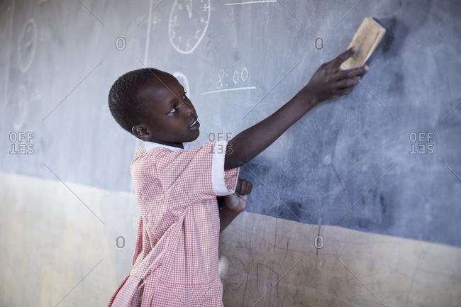 Young girl erases chalkboard in classroom, Kenya