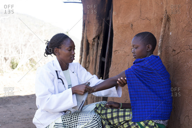 Doctor examines a woman's arm in Maasai village, Africa