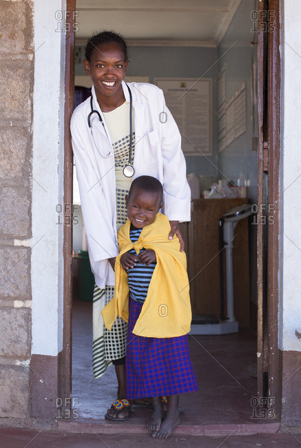 Portrait of doctor with young Maasai child, at clinic, Kenya