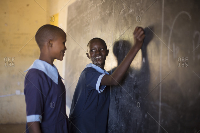 Two girls working together at chalkboard in classroom, Kenya