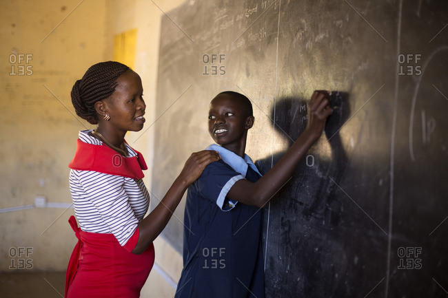 Teacher with female student in classroom, Kenya, Africa