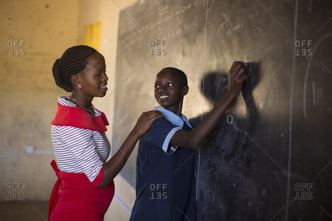 Teacher working with student at chalkboard in classroom, Kenya