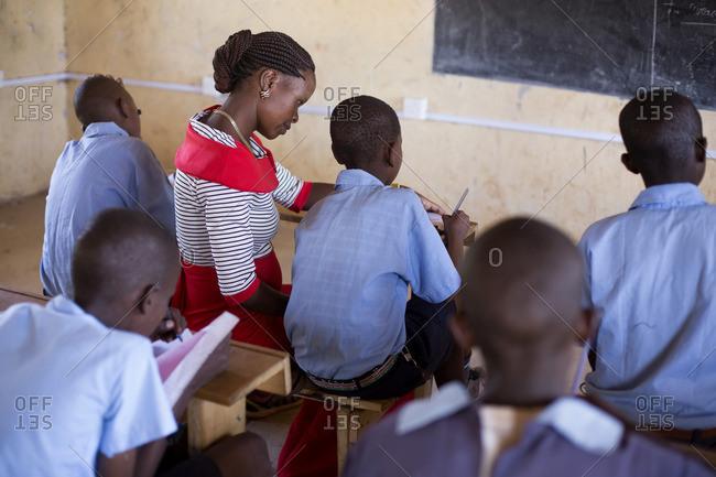 Teacher sitting next to student at desk in classroom, Kenya