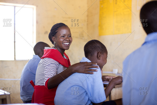 Smiling teacher among her students in classroom, Kenya