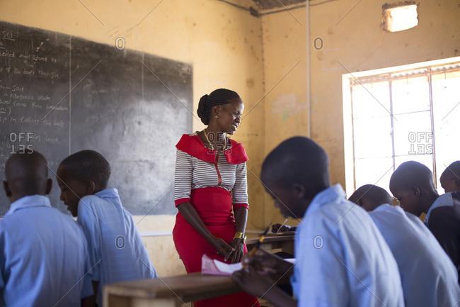 Teacher overlooks her students at work in classroom, Kenya