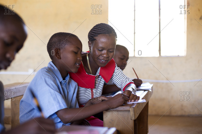 Teacher working with boy on his writing, Kenya, Africa