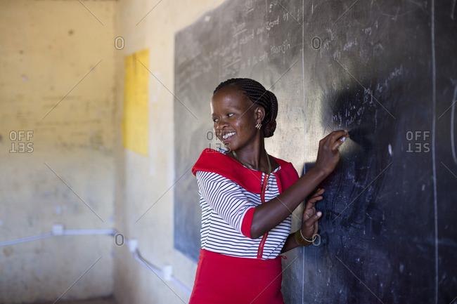 Teacher writing on chalkboard in classroom, Kenya
