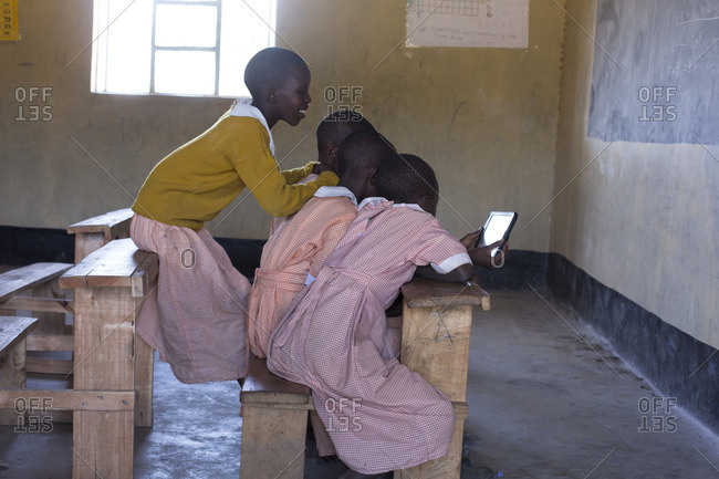 Young girls in classroom looking at tablet, Kenya