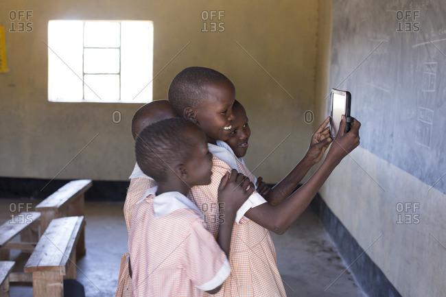 School girls using tablet to take selfie, Kenya, Africa