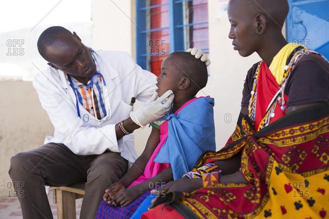 Maasai mother watches as doctor examines her daughter, Kenya