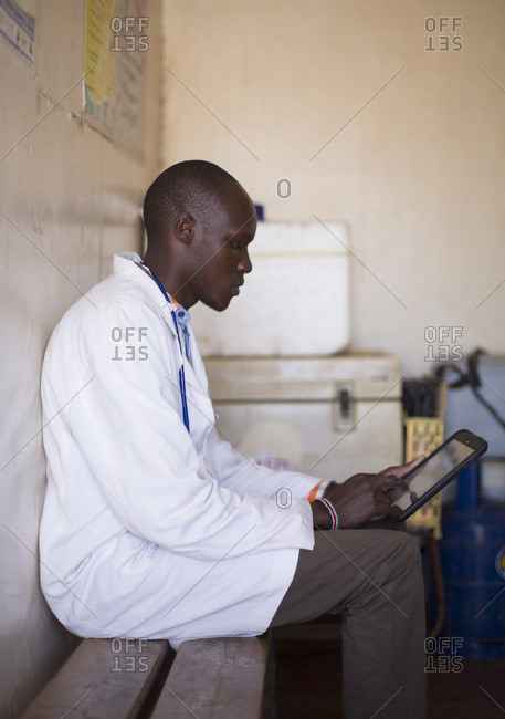 Doctor looking at tablet in clinic, Kenya