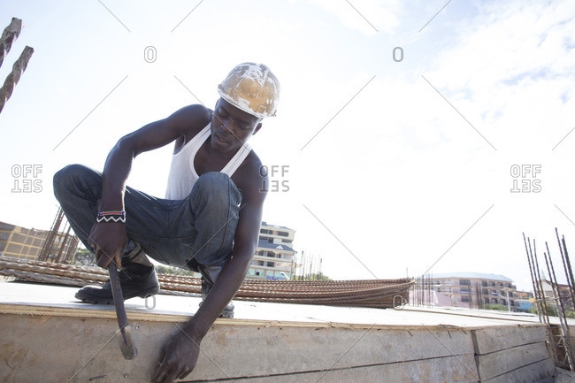 African construction worker nailing board at building site, Kenya