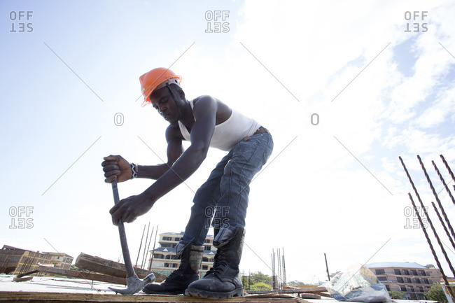 Man removing nail from board at construction site