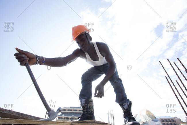 Man pulling out nail from board at construction site