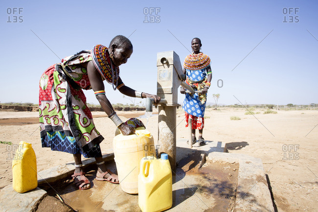 Women from Samburu tribe filling containers with fresh water from well