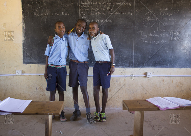 Portrait of three young boys at chalkboard in classroom, Kenya