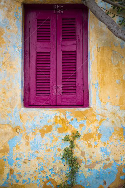 Pink window on a old yellow wall