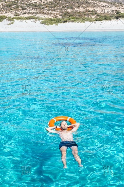 Man floating in the turquoise waters of the Aegean Sea with a float