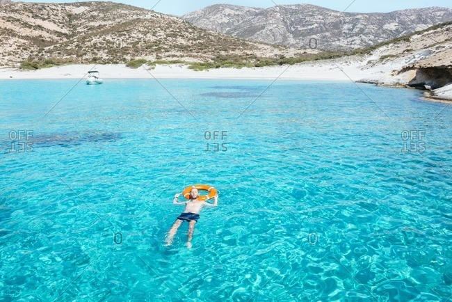 Man floating on a ring in the turquoise waters of the Aegean Sea with a float