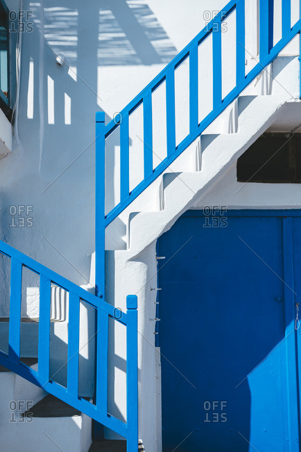 Blue railing and doors of a white house