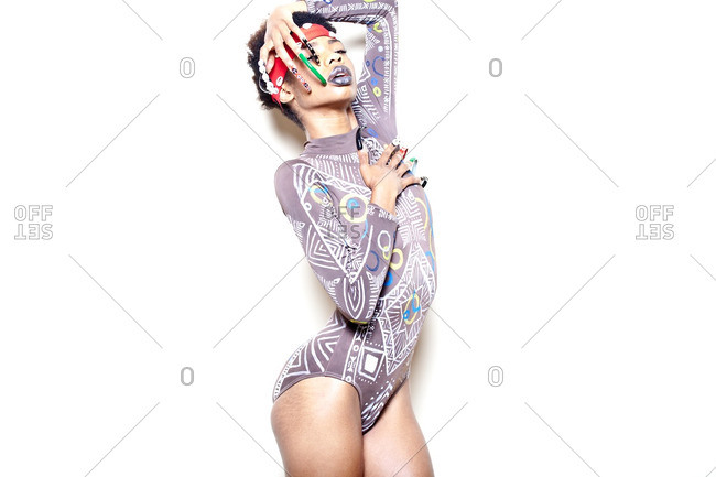 Young woman covering half of her face with her long nails