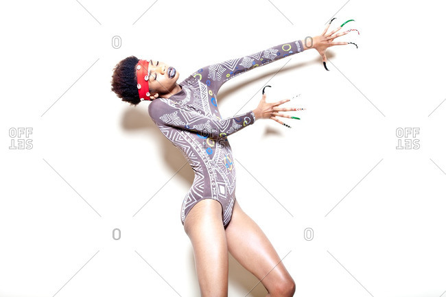 Woman wearing tribal bodysuit reaching her arms out in front of her