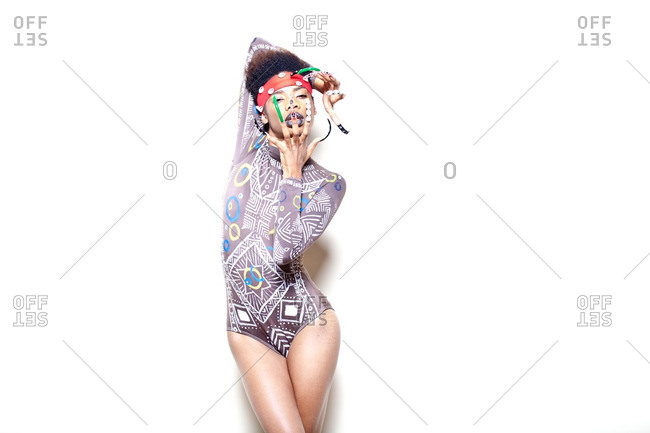 Young woman posing with long nails and tribal bodysuit