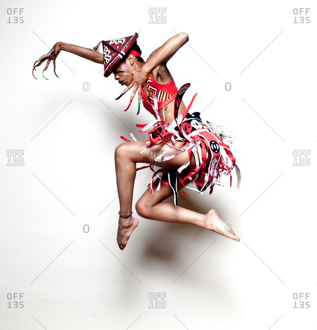 Girl in African warrior costume jumping in mid air