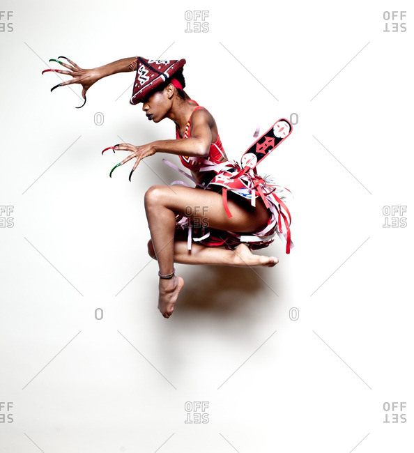 Young woman in African warrior costume jumping in mid air