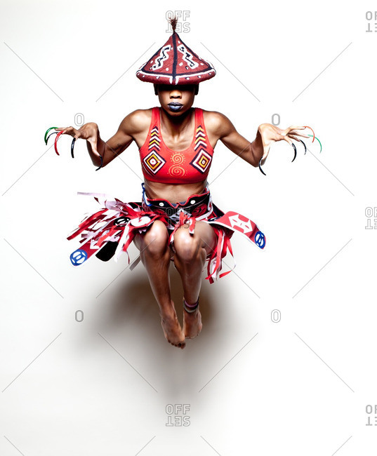 Girl wearing African warrior costume jumping in mid air