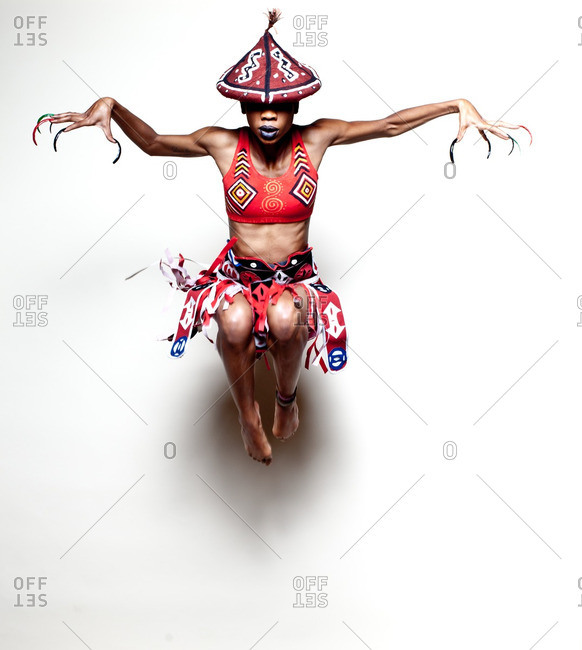 Girl wearing African warrior costume jumping and stretching arms out