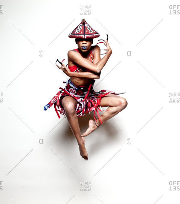 Woman wearing African warrior costume jumping in the air