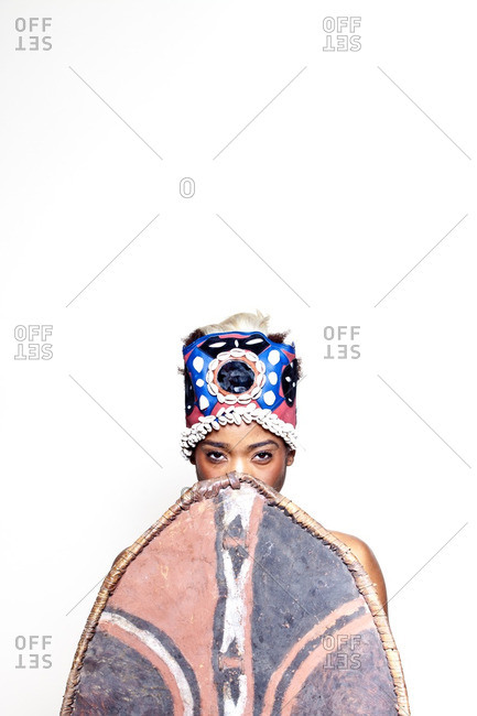 Woman wearing African warrior costume and holding shield