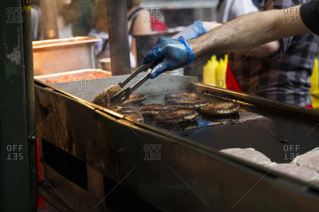 Preparing hamburgers in a market, London, UK