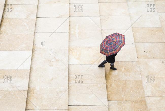 Woman walking in rain in Bilbao, Spain