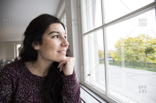 Woman by window with chin on hand