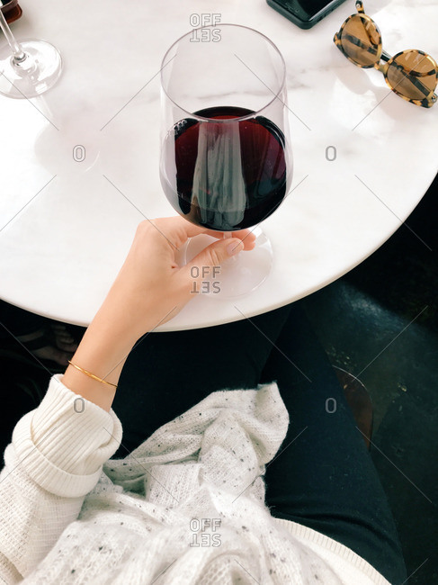 Woman drinking red wine from large glass