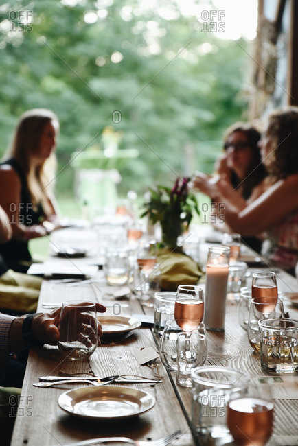 People enjoying blush wine at a dinner party