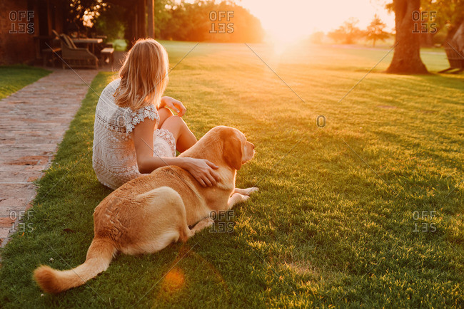 Woman sitting in the grass with her dog watching the sunset