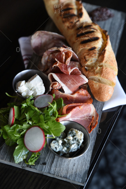 Overhead view of a charcuterie board with bread and salad