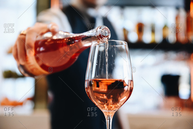 Bartender serving glass of blush wine