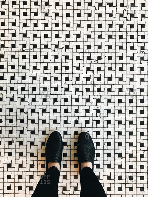 High angle view of feet on black and white pattern tile