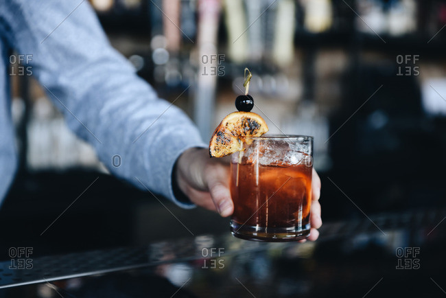 Bartender serving an old fashioned cocktail on a bar