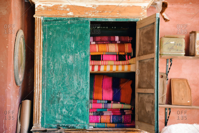 Stacks of folded woven textiles in a cabinet